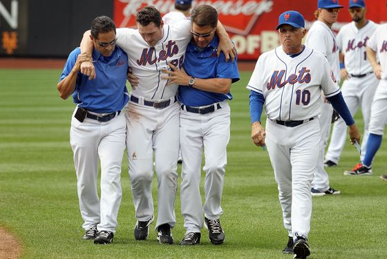 NEW YORK, NY - AUGUST 07:  Daniel Murphy #28 of the New York Mets is helped off the field by head trainer Ray Ramirez (L), trainer Mike Herbst and manager Terry Collins #10 after a seventh inning injury trying to prevent a stolen base against the Atlanta Braves at Citi Field on August 7, 2011 in the Flushing neighborhood of the Queens borough of New York City.  (Photo by Jim McIsaac/Getty Images)