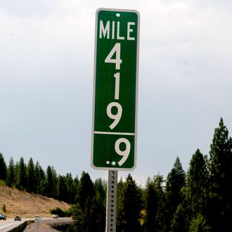 In this Tuesday, Aug. 11, 2015 photo, vehicles pass a 419.9 milepost just south of Coeur d'Alene, Idaho. Idaho joined Colorado in replacing milepost 420 signs with milepost 419.9 designations in an effort to thwart thievery. (Kathy Plonka/The Spokesman-Review via AP) COEUR D'ALENE PRESS OUT; MANDATORY CREDIT
