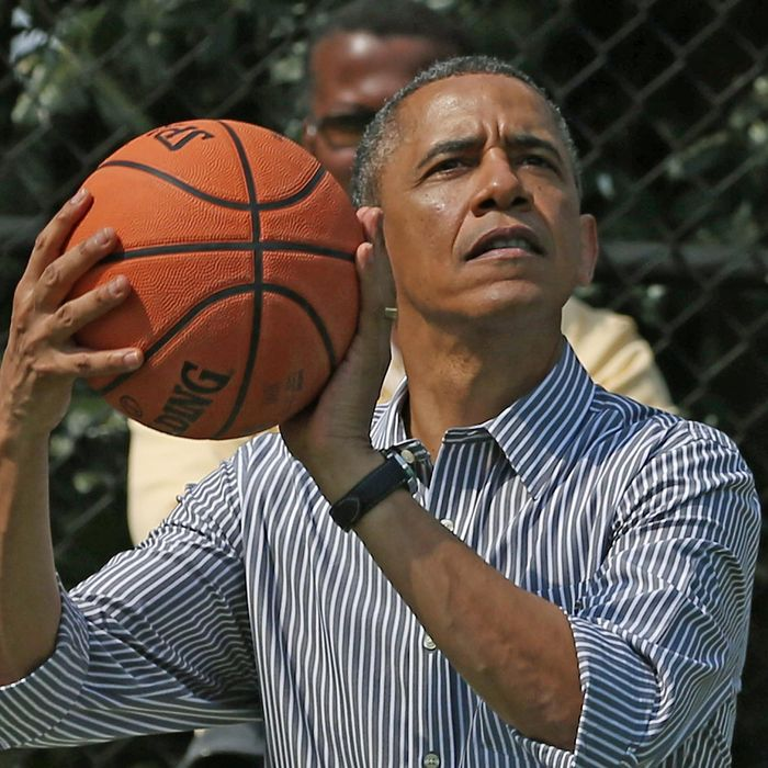 U.S. President Barack Obama plays basketball during the annual Easter Egg Roll on the White House tennis court April 1, 2013 in Washington, DC.