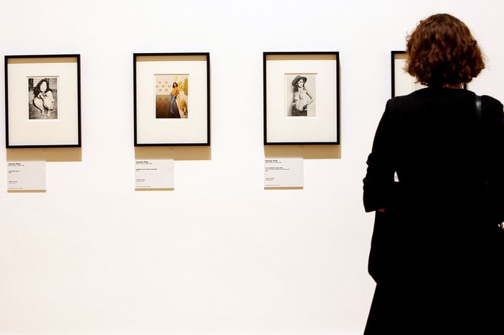 A woman looking at works by Hannah Wilke.