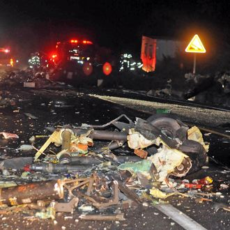 The wreckage of a U.S.AH-64 Apache helicopter is strewn along a road in Wonju, South Korea, Monday, Nov. 23, 2015. The helicopter crashed in South Korea on Monday, killing two people on board, police said.
