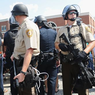 FERGUSON, MO - AUGUST 11: Armed St. Louis County Police Officers stand among citizens during a protest of the shooting death of 18-year-old Michael Brown by a Ferguson police officer, outside Ferguson Police Department Headquarters August 11, 2014 in Ferguson, Missouri. Civil unrest broke out as a result of the shooting of the unarmed black man as crowds looted and burned stores, vandalized vehicles and taunted police officers. Dozens were arrested for various infractions including assault, burglary and theft. (Photo by Michael B. Thomas/Getty Images)