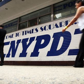People walk by a New York Police Department (NYPD) outpost in Times Square