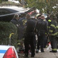 First responders examine an automobile after its driver lost control and plowed into a group of trick-or-treaters Saturday, Oct. 31, 2015 in New York. Three people were killed in the, including a 10-year-old girl. Several others were injured. (AP Photo/David Greene)
