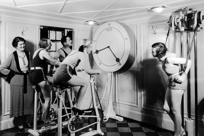 1920s group 4 women one man in exercise gym looking at clock