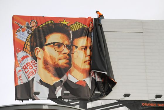"""Workers remove a poster-banner for """"The Interview"""" from a billboard in Hollywood, California, December 18, 2014 a day after Sony announced was cancelling the movie's Christmas release due to a terrorist threat.  Sony defended itself Thursday against a flood of criticism for canceling the movie which angered North Korea and triggered a massive cyber-attack, as the crisis took a wider diplomatic turn."""