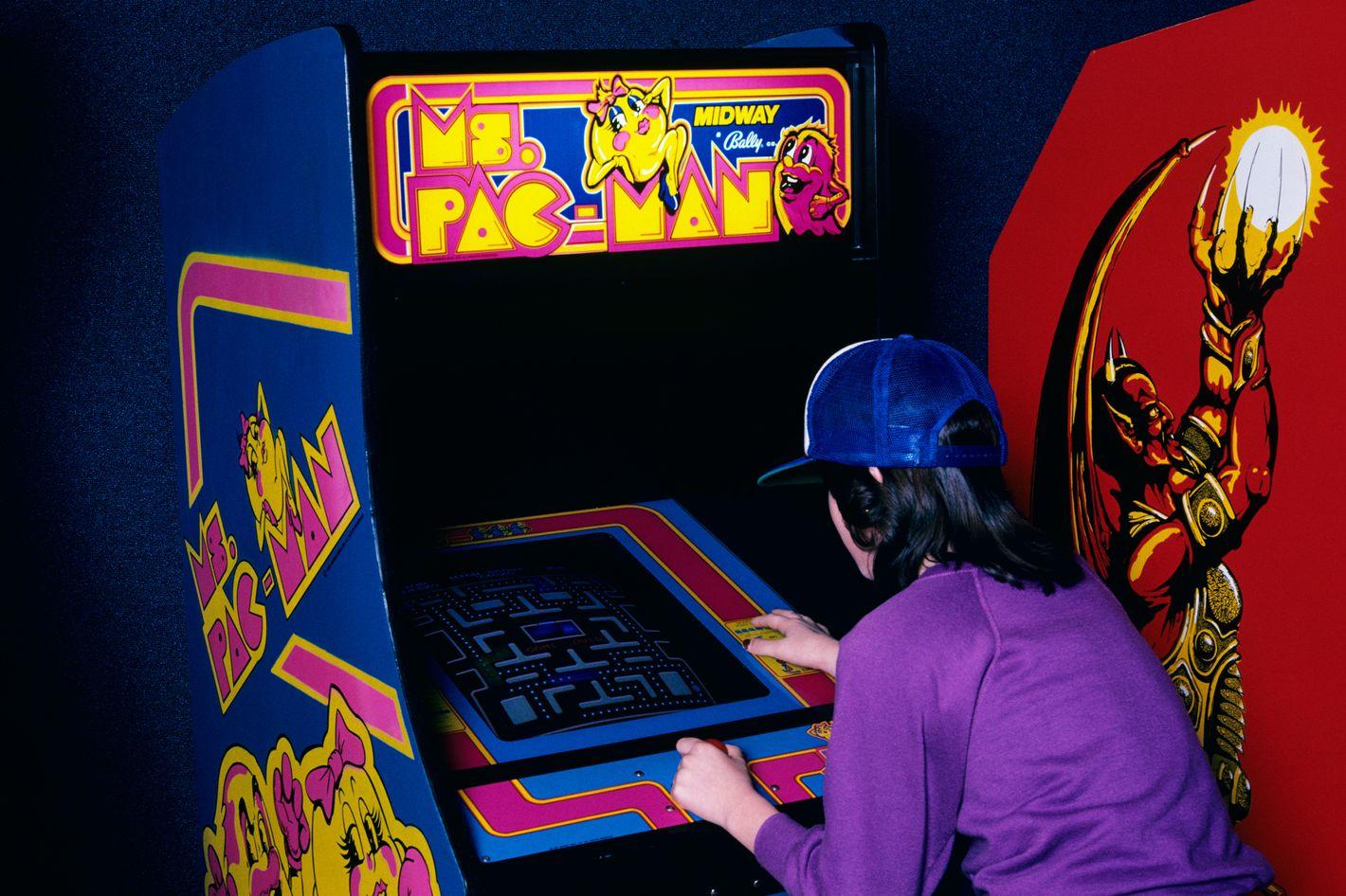Teen Girl Wear Baseball Cap Playing Ms. Pac Man Video Game In Arcade