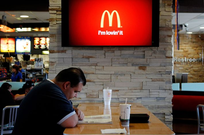 Customer Steven Price sits at a table near a HDTV screen showing the new McDonald's Channel featuring a commerical about McCafe drinks at a McDonald's restaurant, part of the test market for the channel in Norwalk, California October 17, 2011. McDonald's Corp will roll out its own family-friendly, all high-definition television channel to nearly 800 restaurants in Southern and Central California by March. The move is part of an expanded test of the service, which the world's biggest hamburger chain one day hopes to take across the United States. REUTERS/Fred Prouser (UNITED STATES - Tags: BUSINESS FOOD) --- Image by ? FRED PROUSER/Reuters/Corbis