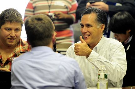 Republican presidential hopeful Mitt Romney gives a thumb up as he joins volounteer to call potential voters at his New Hampshire headquarters in Manchester, New Hampshire, on January 9, 2012.  New Hampshire will hold its Republican primaries on January 10, 2012.