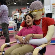 "An employee of Japan's nursing care goods maker Unicare demonstrates an easy chair for cognitively impaired persons ""Yasuragi chair"" at the annual International Home care and Rehabilitation exhibition in Tokyo on October 1, 2014.  The chair can hug the user with the long arms with velcro tape."