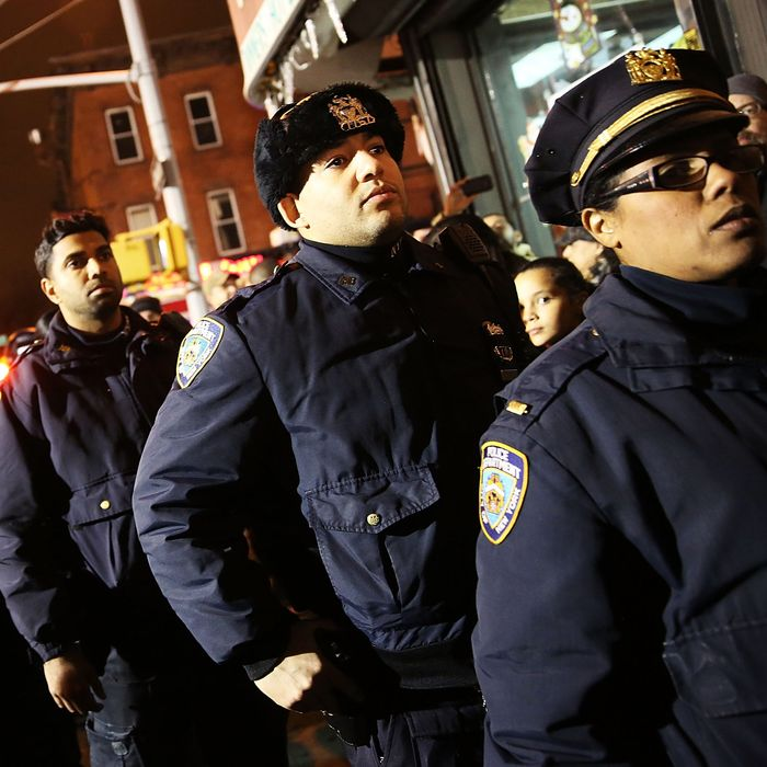 Police officers line-up to pay their respects at a memorial during a vigil for two New York City police officers at the location where they were killed, December 21, 2014 in New York City. The police officers were shot execution style Saturday afternoon as they sat in their marked police car on a Brooklyn street corner. The suspect, who allegedly shot his girlfriend in Baltimore earlier in the day, is believed to have been motivated by the deaths of Eric Garner and Michael Brown. (Photo by Spencer Platt/Getty Images)