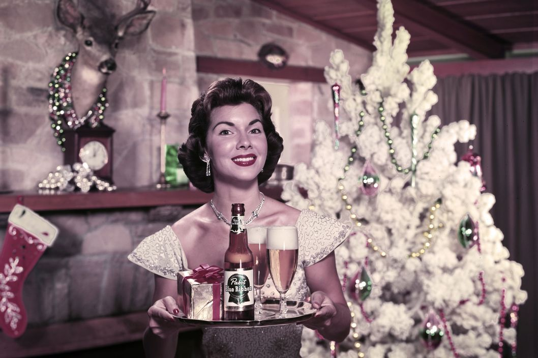 gal with beers on tray and Christmas tree