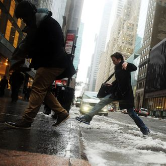 Pedestrians navigate the snow, ice and puddles along Manhattan's streets on February 2, 2015 in New York City. Another winter storm has brought inclement weather to much of the Northeast, canceling schools and hundreds of flights throughout the New York metro area.