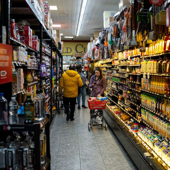 A woman shopping at a New York City Key Food, standing in the juice aisle