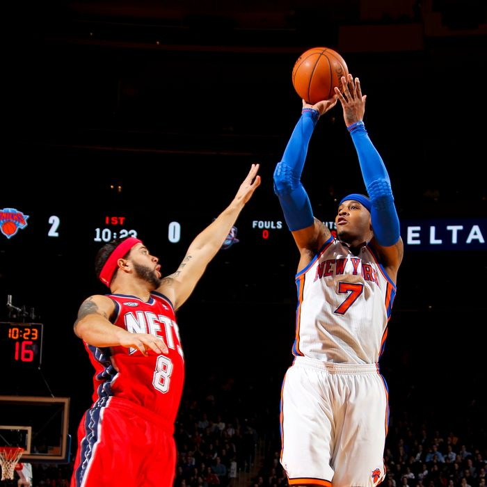 Carmelo Anthony #7 of the New York Knicks shoots over Deron Williams #8 of the New Jersey Nets on February 20, 2012 at Madison Square Garden in New York City.