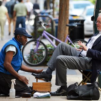 A shoeshiner attends a customer in downtown Washington, DC, on September 19, 2012.