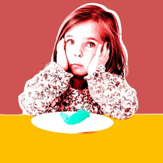 Girl (3-4) sitting at table with plate, close-up