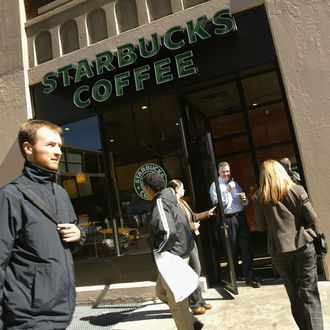 NEW YORK - OCTOBER 5: People walk past a Starbucks coffee shop October 5, 2004 in New York City. As coffee bean costs in the US have risen in the past two months, the Starbucks chain will add an average of 11 cents to the cost of a cup of coffee in its American outlets. (Photo by Spencer Platt/Getty Images)