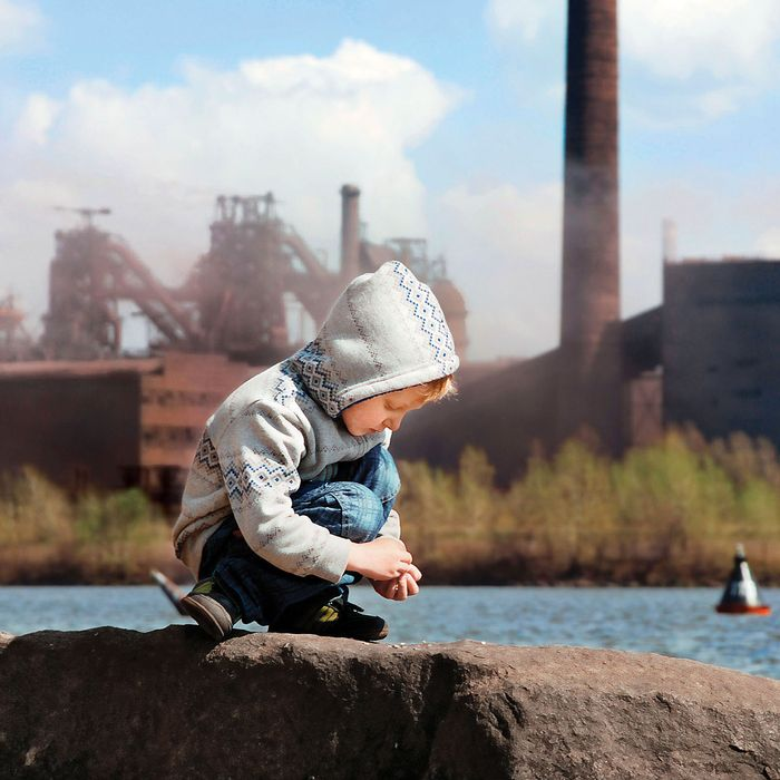 A child playing in front of a metallurgy factory.