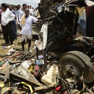 The mangled wreckage of a school bus is pictured as bystanders look on at the scene of the collision between a school bus and a train at Thoopran Mandal of Medak District, about 58 kilometers from Hyderabad, on July 24, 2014.  A passenger train rammed into a school bus in southern India, killing at least 11 children, with fears the death toll could be as high as 25, officials said.