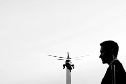 A Secret Service watches as Marine One passes the Washington monument while approaching the South Lawn of the White House with US President Barack Obama on board March 22, 2012 in Washington, DC. President Obama was returning from a two-day trip to Nevada, New Mexico, Oklahoma and Ohio where he stumped the economy and energy.