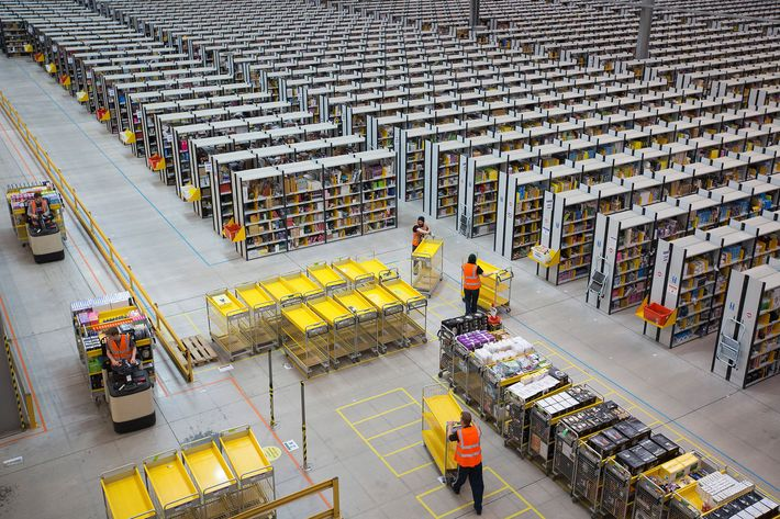 Employees push empty carts as they prepare to process customer orders ahead of shipping at one of Amazon.com Inc.'s fulfillment centers in Rugeley, U.K., on Monday, Dec. 2, 2013. Online retailers in the U.K. are anticipating their busiest day as shoppers flush with end-of-month pay-checks seek Christmas deals on the Web. Photographer: Simon Dawson/Bloomberg via Getty Images