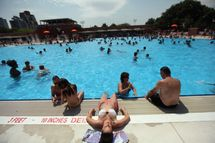 People bathe on opening day of the newly renovated McCarren Park Pool on June 28, 2012 in the Brooklyn borough of New York City. The historic 37,000 square-foot pool had been closed since 1983 but has been rejuvenated by a $50 million restoration. Today is the first day New York City public pools opened for the summer.