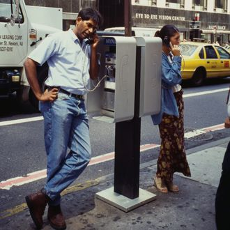 A man and woman using a telephone booth on the street in New York City, USA, 1995.