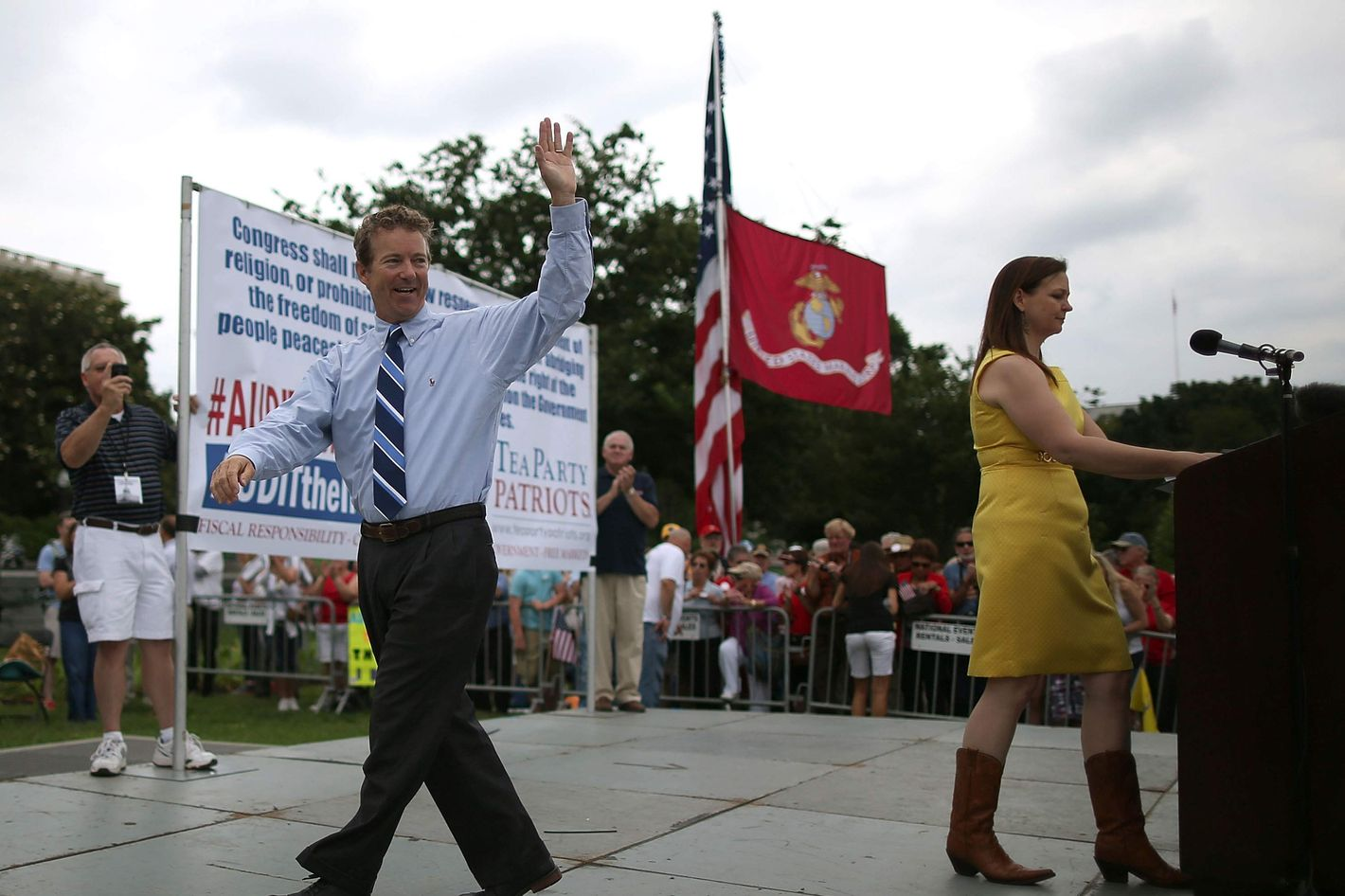 Sen. Rand Paul (R-KY) (L) waves to the crowd while Jenny Beth Martin (R) introduces the next speaker during a Tea Party rally in front of the U.S. Capitol, June 17, 2013 in Washington, DC. The group Tea Party Patriots hosted the rally to protest against the Internal Revenue Service's targeting Tea Party and grassroots organizations for harassment.