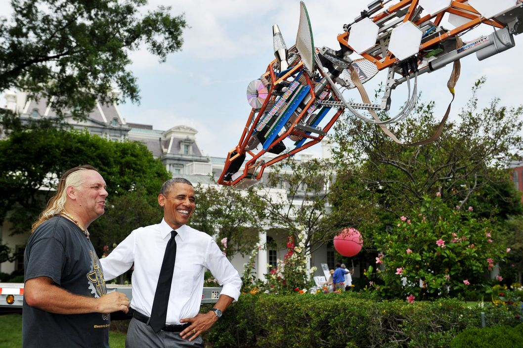 US President Barack Obama(R) and Lindsay Lawlor view Lawlor's robotic giraffe while viewing Maker Faire projects on the South Lawn of the White House on June 18, 2014 in Washington, DC. AFP PHOTO/Mandel NGAN        (Photo credit should read MANDEL NGAN/AFP/Getty Images)