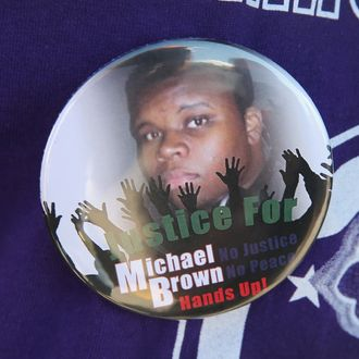 FERGUSON, MO - AUGUST 13: A resident wears a button featuring a picture of Michael Brown during a press conference with Police Chief Thomas Jackson who was fielding questions related to the shooting death of Brown on August 13, 2014 in Ferguson, Missouri. Brown was shot and killed by a Ferguson police officer on Saturday. Ferguson has experienced three days of violent protests since the killing. (Photo by Scott Olson/Getty Images)