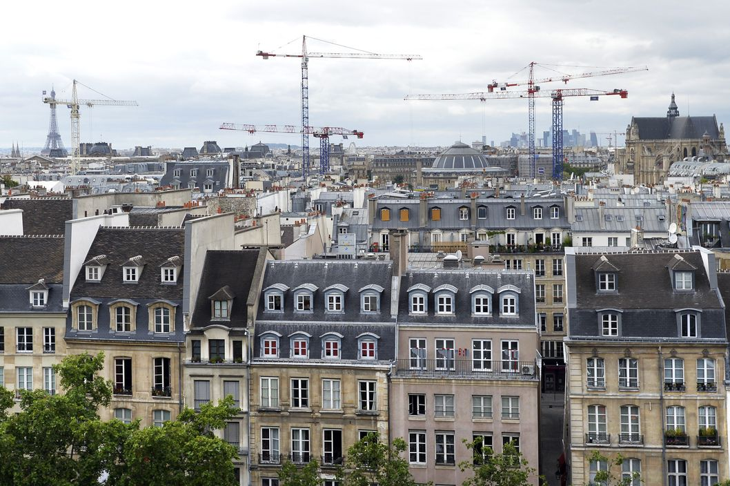 A general view shows rooftops and cranes on July 30, 2013 in Paris with the Eiffel tower (L) in the background.