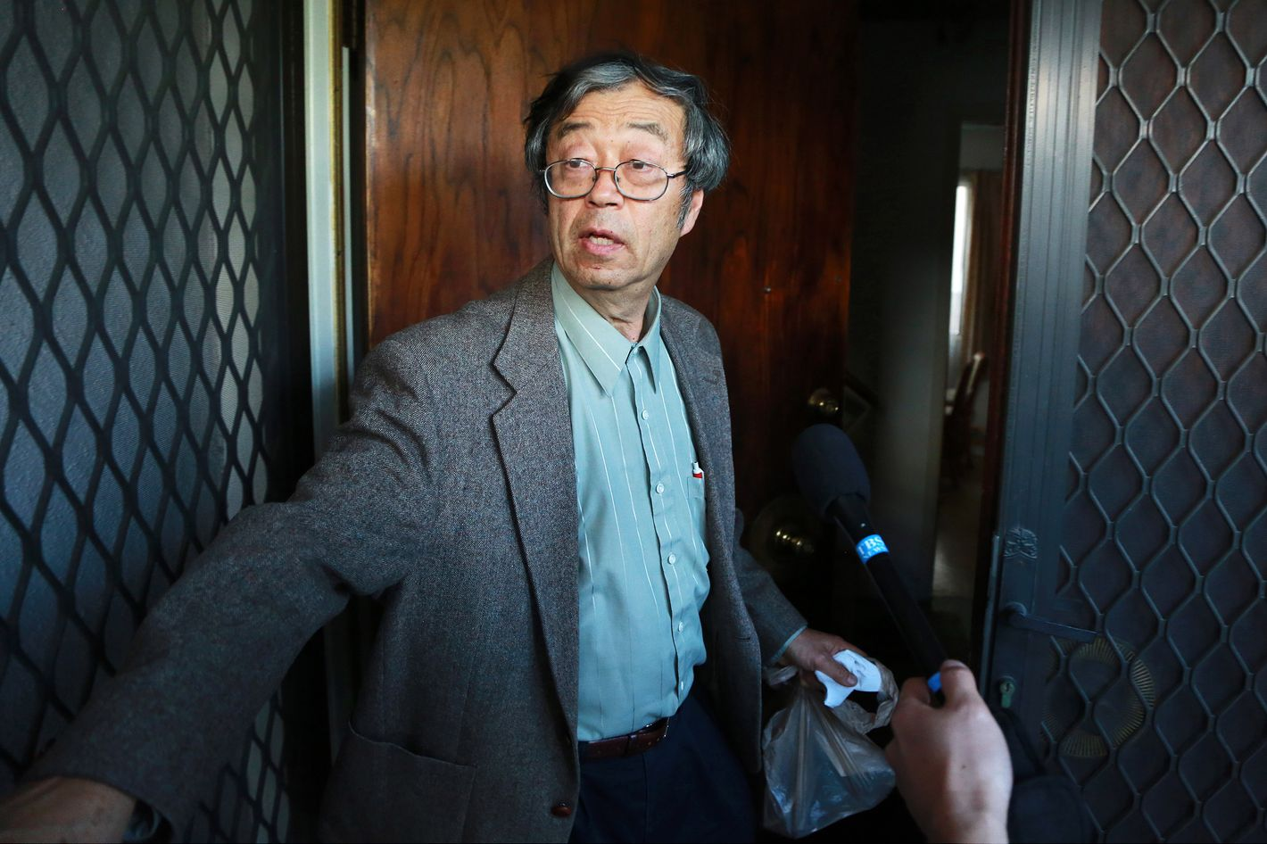 Dorian S. Nakamoto, identified by Newsweek magazine as the founder of Bitcoin, stands surrounded by members of the media as he arrives home in Temple City, California, U.S., on Thursday, March 6, 2014. Nakamoto, a 64-year-old physicist, denied involvement in the digital currency before leading reporters on a multi-vehicle car chase and entering an Associated Press bureau.