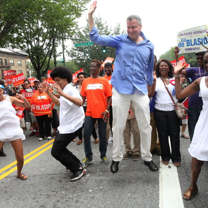 Bill de Blasio, running in the NYC Mayors race, foreground second from right, dances with his family as he makes his way along Eastern Parkway in the Brooklyn borough of New York during the West Indian Day Parade, Monday, Sept. 2, 2013. (AP Photo/Tina Fineberg)
