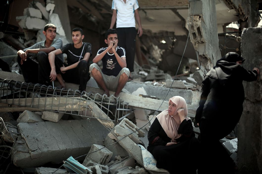 Palestinians sit on the ruins of a building destroyed by Israeli assaults staged within the scope of Operation Protective Edge in Gaza City, Gaza on July 24, 2014. The Palestinian death toll from Israel's ongoing offensive against the Gaza Strip has risen to 732.