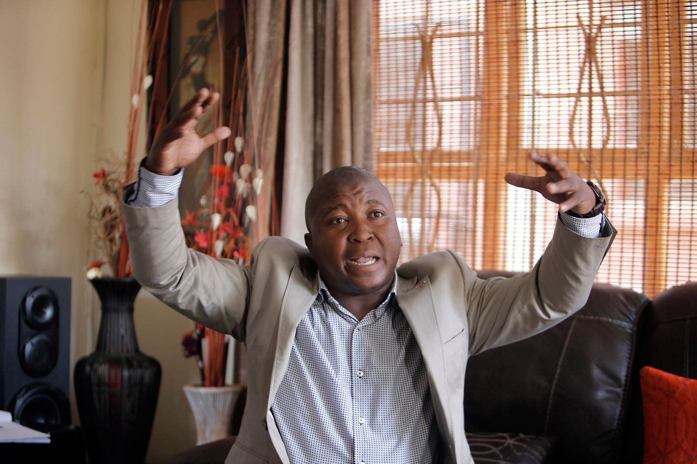 Thamsanqa Jantjie gesticulates at his home during an interview with the Associated Press in Johannesburg, South Africa,Thursday, Dec. 12, 2013. Jantjie, the man accused of faking sign interpretation next to world leaders at Nelson Mandela's memorial, told a local newspaper that he was hallucinating and hearing voices.