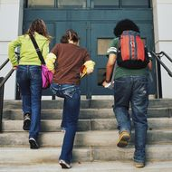 Two teenage girls and teenage boy (14-16) walking up school steps, rear view