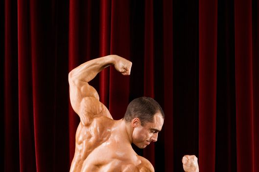 Hispanic male body builder flexing on stage