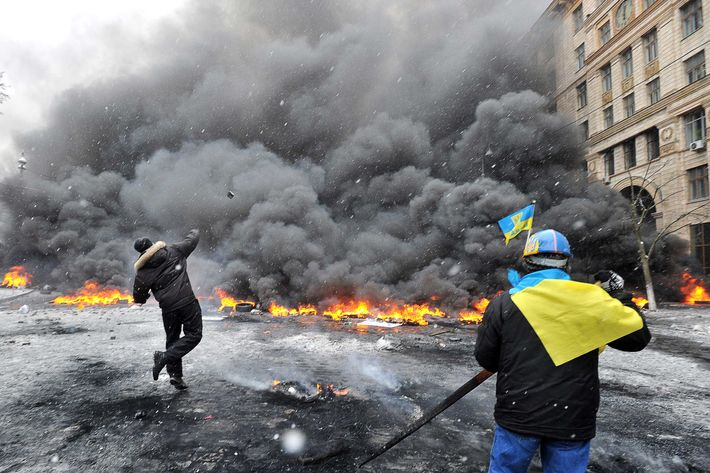 Protestors throw stones as they clash with police in the center of Kiev on January 22, 2014. At least two activists were shot dead today as Ukrainian police stormed protesters' barricades in Kiev, the first fatalities in two months of anti-government protests. Pitched battles raged in the centre of the Ukrainian capital as protesters hurled stones at police and the security forces responded with tear gas and rubber bullets. AFP PHOTO / GENYA SAVILOV        (Photo credit should read GENYA SAVILOV/AFP/Getty Images)