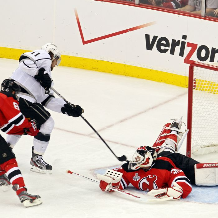 Anze Kopitar #11 of the Los Angeles Kings shoots the game winning goal in overtime against Dainius Zubrus #8 and Martin Brodeur #30 of the New Jersey Devils during Game One of the 2012 NHL Stanley Cup Final at the Prudential Center on May 30, 2012 in Newark, New Jersey.