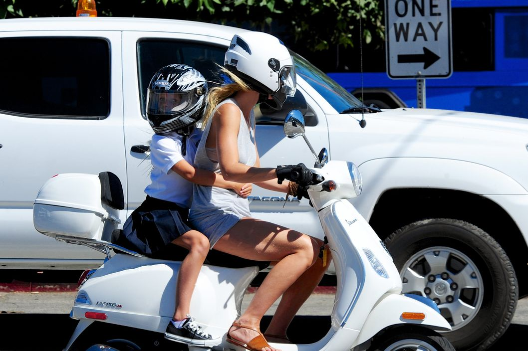 Gwyneth Paltrow and Chris Martin drive around town on their matching white Vespa scooters. They eventually grab their kids, daughter Apple and son Moses, and drive off together.  And while they all wear helmets it seems the famous couple does not take other safety measures very seriously in regards to their attire and shoes. They also choose to not abide by the rules of the road as Paltrow is seen driving recklessly and Martin carelessly crosses a double yellow line to drive on the wrong side of the road with his son in tow.