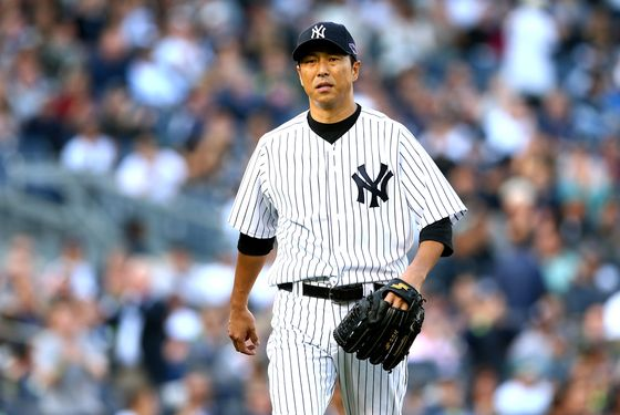 Hiroki Kuroda #18 of the New York Yankees walks back to the dugout at the end of the top of the first inning against the Detroit Tigers during Game Two of the American League Championship Series at Yankee Stadium on October 14, 2012 in the Bronx borough of New York City.
