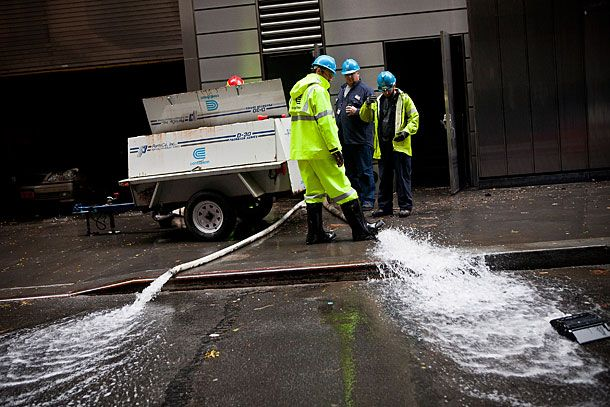NEW YORK, NY - OCTOBER 30:  Con Edison employees monitor the drainage of water being pumped out of Seven World Trade Center, caused by Hurricane Sandy, on October 30, 2012 in the Financial District of New York, United States. The storm has claimed at least 33 lives in the United States, and has caused massive flooding accross much of the Atlantic seaboard.  (Photo by Andrew Burton/Getty Images)