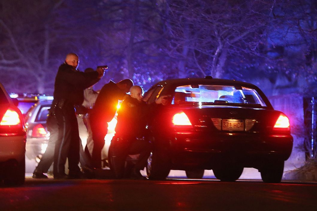 WATERTOWN, MA - APRIL 19:  (ALTERNATE CROP) Police with guns drawn search for a suspect on April 19, 2013 in Watertown, Massachusetts.  Earlier, a Massachusetts Institute of Technology campus police officer was shot and killed late Thursday night at the school's campus in Cambridge. A short time later, police reported exchanging gunfire with alleged carjackers in Watertown, a city near Cambridge. It's not clear whether the shootings are related or whether either are related to the Boston Marathon bombing.  (Photo by Mario Tama/Getty Images)