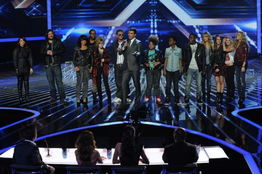 Host Steve Jones (C) and the top 10 contestants stand before the judges on THE X FACTOR airing Thursday, Nov. 17.