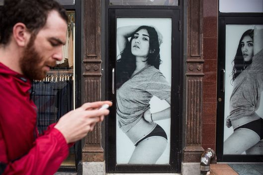 A man walks past an American Apparel store on June 19, 2014 in New York City. American Apparel's board has voted to remove the company's controversial CEO, Dov Charney.