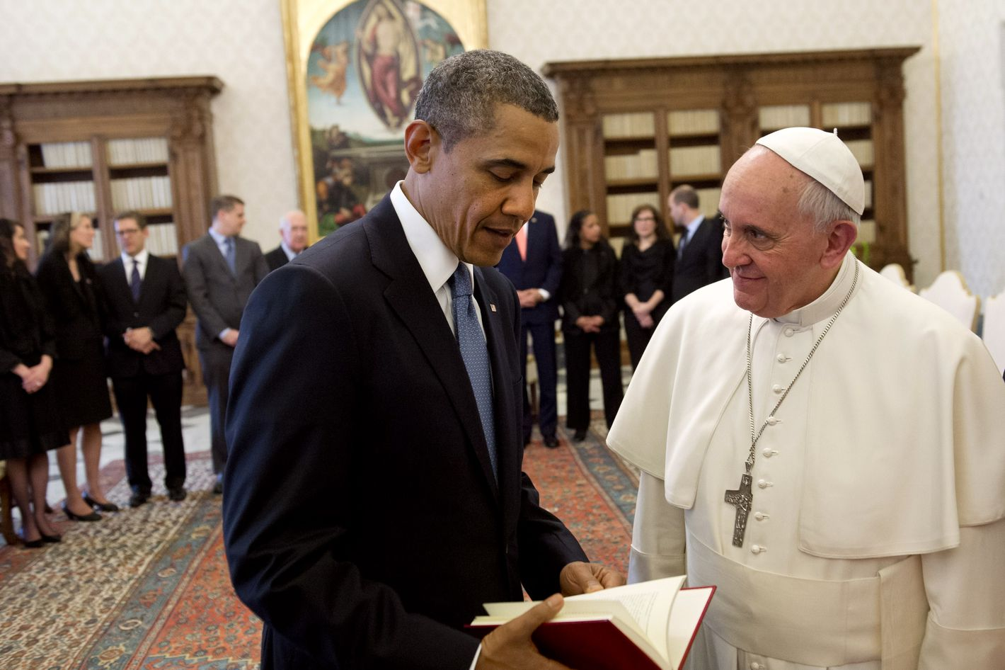 Pope Francis (R) presents a book to US President Barack Obama as they exchange gifts during a private audience on March 27, 2014 at the Vatican. The meeting at the Vatican comes as a welcome rest-stop for Obama during a six-day European tour dominated by the crisis over Crimea, and the US leader will doubtless be hoping some of the pope's overwhelming popularity will rub off on him.    AFP PHOTO / SAUL LOEB