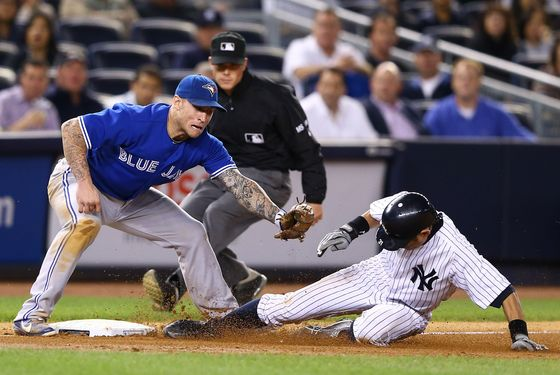 NEW YORK, NY - SEPTEMBER 19:  Ichiro Suzuki #31 of the New York Yankees steals third base as Brett Lawrie #13 of the Toronto Blue Jays is late with the tag during their game on September 19, 2012 at Yankee Stadium in the Bronx borough of New York City  (Photo by Al Bello/Getty Images)