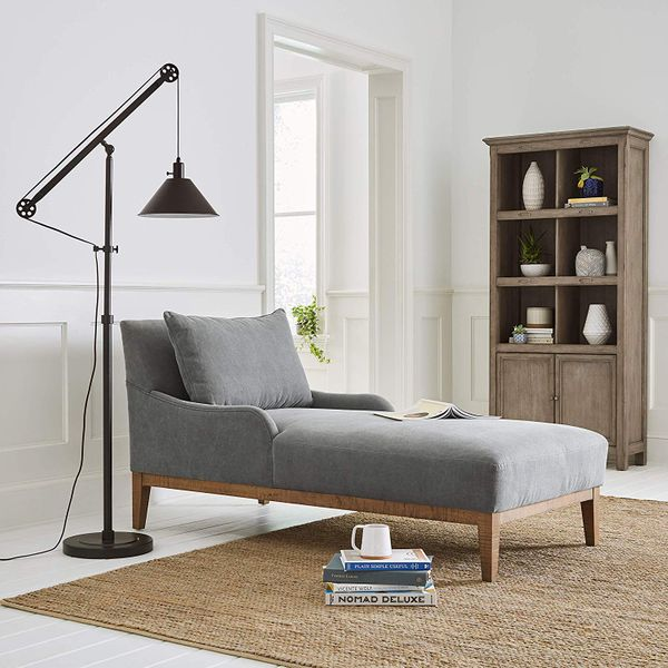 A rustic black Wayfair floor lamp a pulley system next to a grey settee, a brown rug, and a stack of books. The Strategist - Very Tasteful Lamps from Amazon's Rivet and Stone and Beam Are on Sale