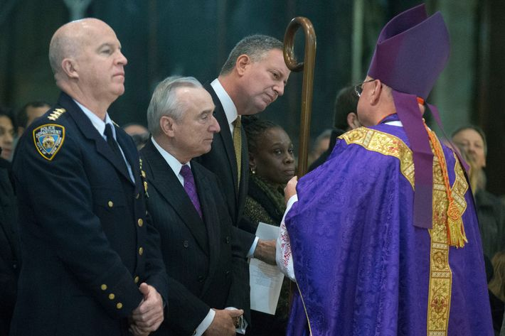 From left, NYPD's Chief of Department James O'Neill, NYPD Commissioner Bill Bratton, New York City Mayor Bill de Blasio, and New York City first lady Chirlane McCray greet Cardinal Timothy Dolan as they attend Mass at St. Patrick's Cathedral, Sunday, Dec. 21, 2014, in New York. An armed man walked up to two New York City police officers sitting inside a patrol car and opened fire Saturday afternoon, killing both before running into a nearby subway station and committing suicide, police said. (AP Photo/John Minchillo)